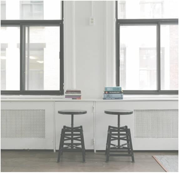 two stools facing two windows with two stacks of text books